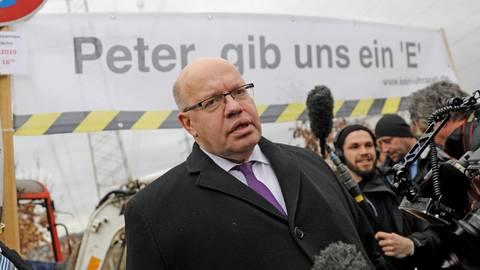 Peter Altmaier beim Trassenbesuch in Niedernhausen. Das E auf dem Transparent steht für Erdverkabelung.  Foto: René Vigneron