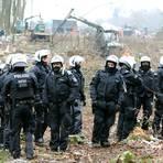 """Polizisten stehen vor einem sogenannten """"Harvester"""", der für die A49-Trasse Bäume rodet. Im Dannenröder Forst werden die letzten Baumhäuser geräumt. Seit Monaten protestieren Umweltaktivisten gegen die Rodung von Wald für den Weiterbau der Autobahn A49 in Mittelhessen.  Foto: dpa"""