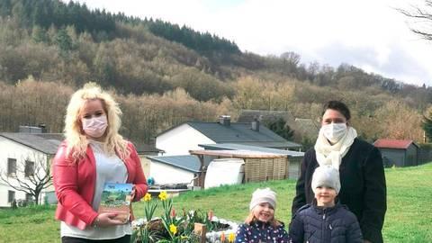 """Janine Theel von der Taunus Hausbau GmbH (l.) bringt der Kita """"Tigerente"""" in Barig-Selbenhausen Infos rund um Insekten und ein neues Bienenhaus mit. Darüber freuen sich Kita-Leiterin Marion Weber und die Kinder.  Foto: Janine Theel"""