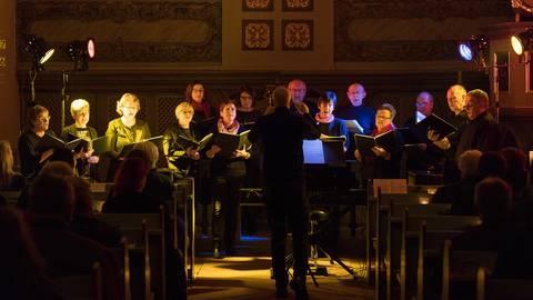 """Getaucht in farbiges Licht, verbreiteten die """"Wiesbach Voices"""" beim Benefizkonzert Weihnachtsstimmung. Foto: BilderKartell/Carsten Selak"""
