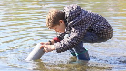 Durch ein Rohr mit Glasboden betrachtet Julian Reitz beim Schülerprojekt mit dem ASV Rotauge den Grund des Sees am Braunshardter Tännchen. Foto: Vollformat/Marc Schüler