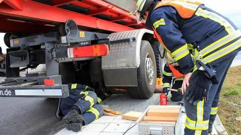 Ein Lkw mit eingeklemmter Person. Mit Unterbauholz versuchen die Feuerwehrkräfte, den notwendigen Freiraum zu schaffen.   Foto: