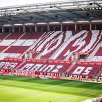 """Die 05-Fans haben ihre Fankurve mit weißen T-Shirts auf den Stühlen so präpariert, dass auf den Stühlen das Vereinslogo und der Schriftzug """"Für immer Mainz 05 e.V."""" zu sehen war. Foto: Lukas Görlach"""