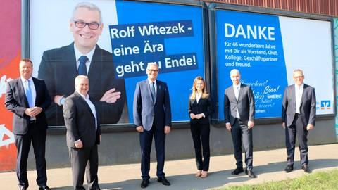 Im Schiffenberger Weg in Gießen, dem Sitz der Volksbank Mittelhessen, wurde zur Verabschiedung von Rolf Witzezek (3.v.li.) ein Plakat gestaltet.  Foto: Voba