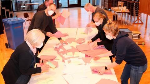 Alle Stimmzetteln für die Kommunalwahl aus einem der vier Gladenbacher Wahllokale liegen auf dem Tisch - zunächst werden diese sortiert. Foto: Michael Tietz