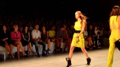 Models auf dem Catwalk - und die Promis direkt in der ersten Reihe dabei. Foto: Anja Kossiwakis