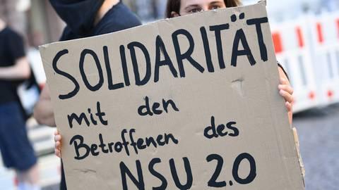 Ein Demonstrantin hält während einer früheren Kundgebung in der Wiesbadener Innenstadt ein Plakat mit der Aufschrift «Solidarität mit den Betroffenen des NSU 2.0». Ein mutmaßlicher Verfasser von rechtsextremen Drohschreiben mit dem Absender «NSU 2.0» ist in Berlin bei einer Wohnungsdurchsuchung festgenommen worden.  Foto: Arne Dedert/dpa