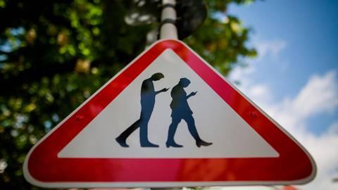 Vor einer Schule warnt dieses Schild vor Menschen, die nur noch mit Blick aufs Smartphone umherlaufen. Foto: dpa