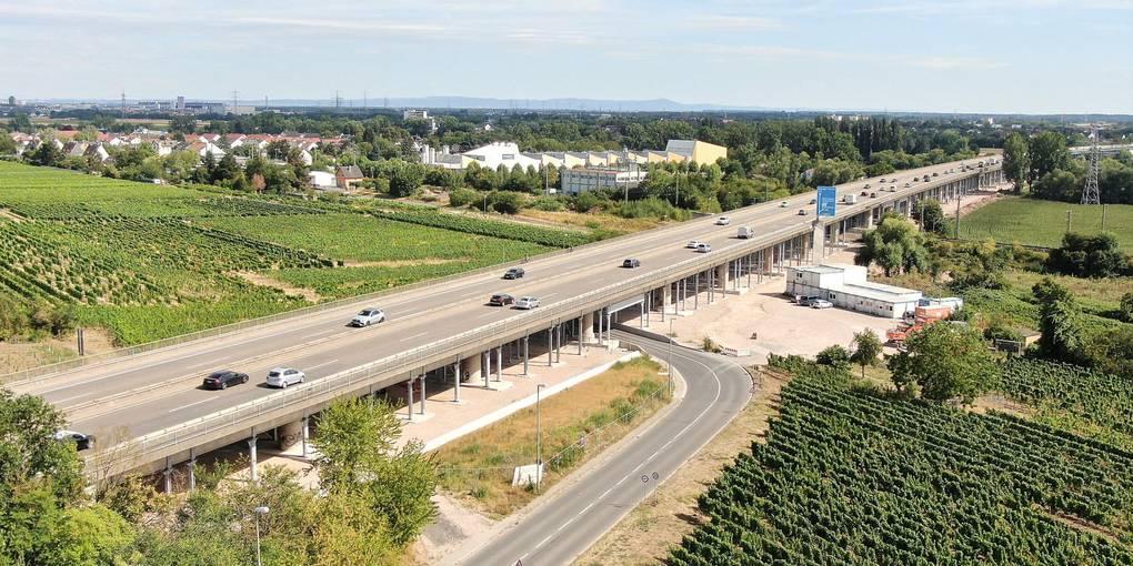 Die Vorlandbrücke bei Hochheim muss erneuert werden. Ihre sichere Standzeit ist seit Dezember 2019 abgelaufen. Die Stützpfeiler stehen. Die alte Brücke wird auf der ganzen Länge (850 m) in der Mitte aufgeschnitten. Die neue Brücke wird je zur Hälfte rechts und links neben dem vorhandenen Bauwerk vorgefertigt, damit der Verkehr vierspurig weiter fließen kann und dann im Querverschub an die vorgesehene Stelle geschoben. Stählerne Pfosten dienen als Verschiebebahnen für die alten und die neuen Brückenteile. Foto: Hessen Mobil / Maurice Kaluscha